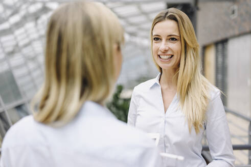 Portrait of young businesswoman smiling at colleague in office - JOSF03848