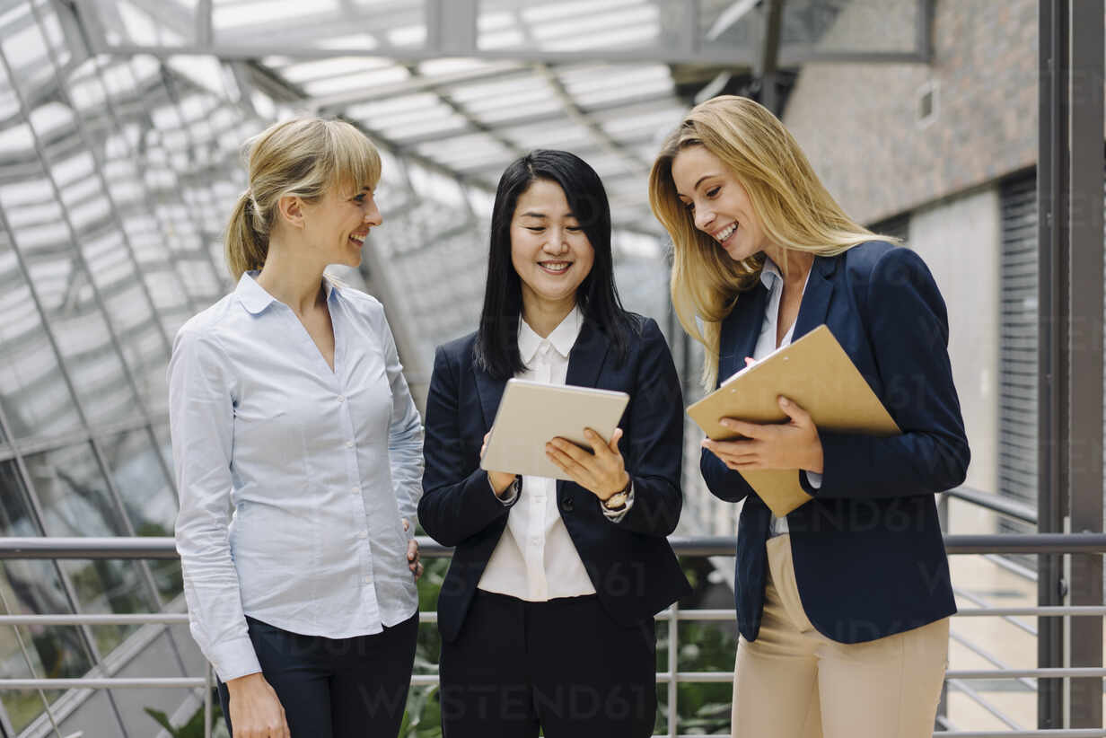 Three businesswomen with tablet talking in modern office building - JOSF03875 - Joseffson/Westend61