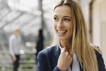 Portrait of a happy young businesswoman in office with colleagues in background - JOSF03881