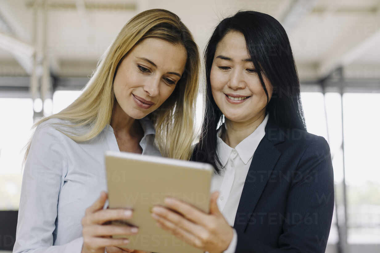 Two businesswomen sharing tablet in office - JOSF03890 - Joseffson/Westend61