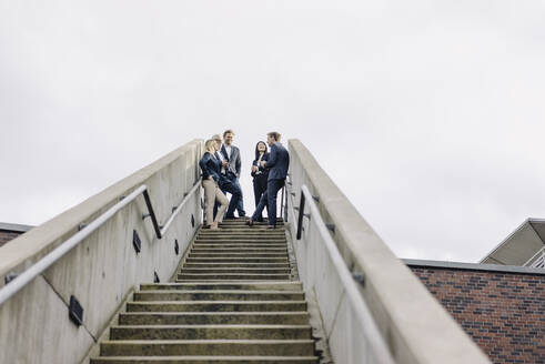Business people standing on exterior stair - JOSF03947