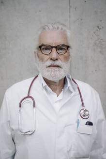 Portrait of a serious doctor at a concrete wall - JOSF03953
