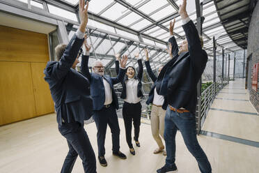 Happy business people cheering in modern office building - JOSF03956