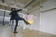 Businessman kicking man dressed up as a ballerina in office - JOSF03959
