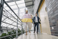 Businessman and man dressed up as a ballerina running in modern office building - JOSF03962