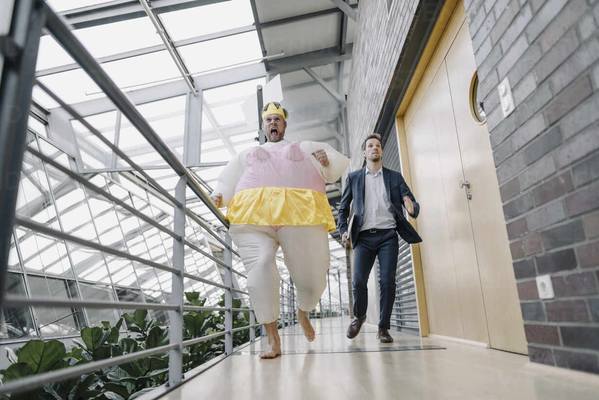 Businessman and man dressed up as a ballerina running in modern office building - JOSF03962 - Joseffson/Westend61