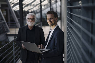 Portrait of two businessmen using laptop in office - JOSF03968