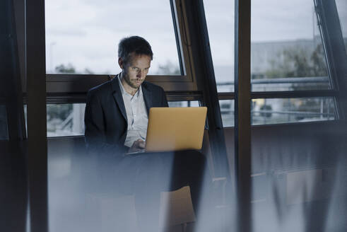Businessman at the window in office working late using laptop - JOSF03971