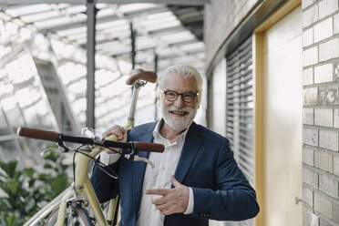 Portrait of a happy senior businessman with a bike in a modern office building - JOSF03977