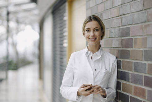 Portrait of a confident female doctor leaning against a brick wall - JOSF03989