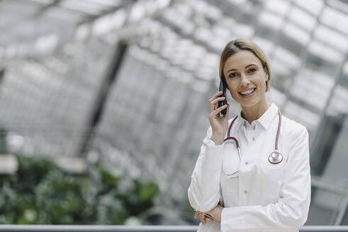 Portrait of a smiling female doctor on the phone - JOSF04007
