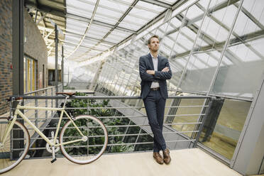 Businessman with bicycle in modern office building - JOSF04028