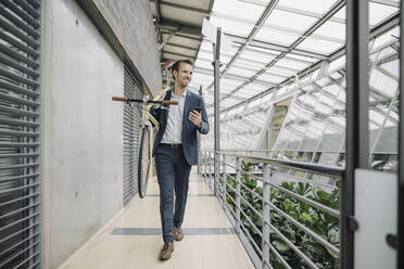 Smiling businessman with cell phone carrying bicycle in modern office building - JOSF04031