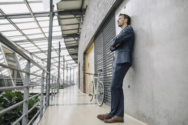 Businessman with closed eyes leaning against a wall in modern office building - JOSF04034