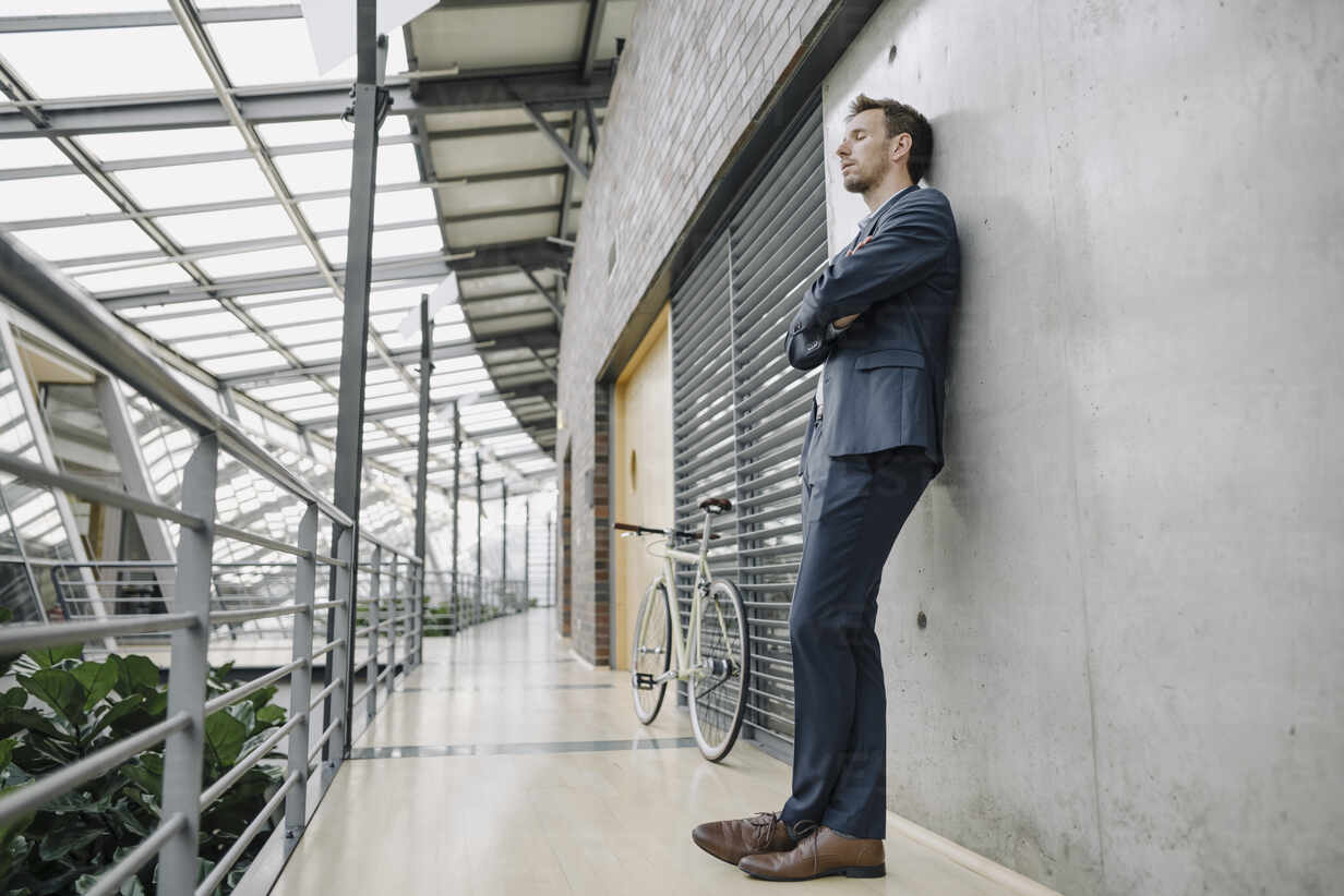 Businessman with closed eyes leaning against a wall in modern office building - JOSF04034 - Joseffson/Westend61