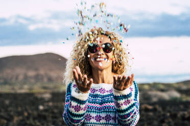 Happy blond woman throwing confetti in the air, Tenerife, Spain - SIPF02098