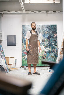Artist standing in his studio, holding paint brush - PESF01721