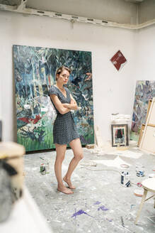 Young artist standing in her studio, with arms crossed - PESF01742
