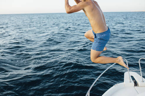 Young man jumping into the sea from a boat - MIMFF00028