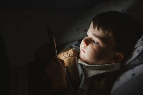 Portrait of little boy lying in bed using smartphone at night - LJF01077