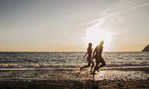 Young couple running at the beach during sunset - LJF01091