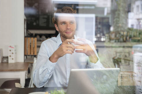 Young businessman with coffee cup and laptop in a cafe - MOEF02700