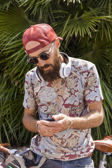 Mature man with red basecap, sunglasses and white headphones using smartphone - TCF06223