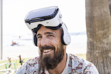 Smiling mature man with virtual reality glasses - TCF06232