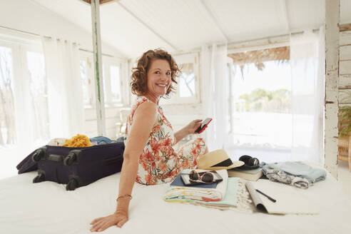 Portrait happy woman unpacking suitcase on beach house bed - HOXF04532