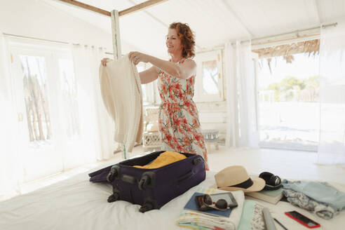 Woman unpacking suitcase in beach hut bedroom - HOXF04544