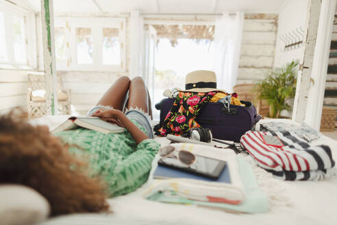 Young woman with book relaxing on bed next to suitcase and belongings in beach hut bedroom - HOXF04562