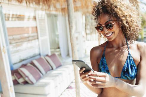 Happy young woman in bikini using smart phone on sunny beach hut patio - HOXF04565