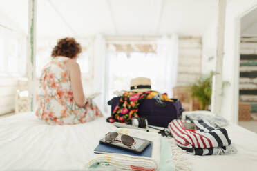 Woman unpacking suitcase in beach house bedroom - HOXF04568