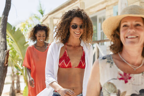 Mother and adult daughters walking outside sunny beach hut - HOXF04577