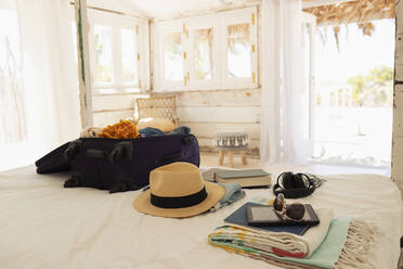 Suitcase, sun hat, sunglasses, book and digital tablet on beach house bed - HOXF04595