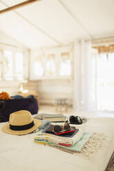 Suitcase, sun hat, sunglasses and book on beach hut bed - HOXF04604