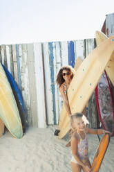 Portrait happy mother and daughter with surfboard on sunny beach - HOXF04625