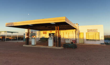 Abandoned gas station and garage at sunset - HOXF04634