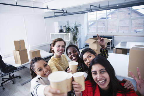 Portrait happy businesswomen celebrating new office - HOXF04691