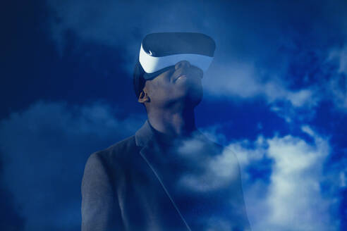 Double exposure businessman with virtual reality simulator glasses against blue sky with clouds - CAIF23384