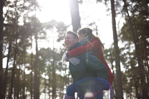 Happy, playful couple piggybacking in sunny woods - CAIF23519
