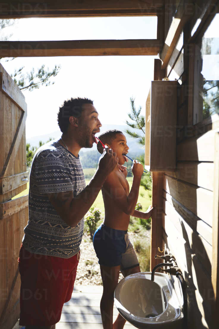 Father And Son Brushing Teeth At Sunny Campsite Bathroom Mirror Caif23627 Trevor Adeline Westend61