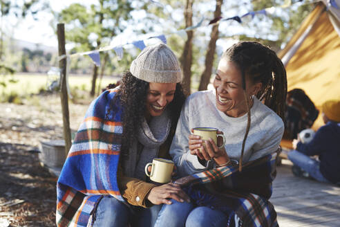 Happy, carefree lesbian couple laughing, drinking coffee at campsite - CAIF23693