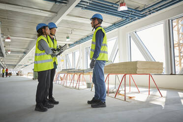 Full length of female and male engineers discussing at construction site - MASF15248