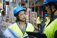 Female engineer discussing with coworker at construction site - MASF15269
