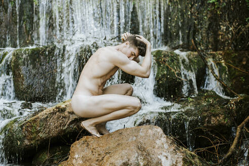 Nude young man in front of a waterfall - MIMFF00033
