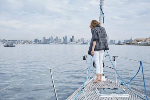 Woman enjoying sea view on bow of sailboat, San Diego, California, USA - CUF53820