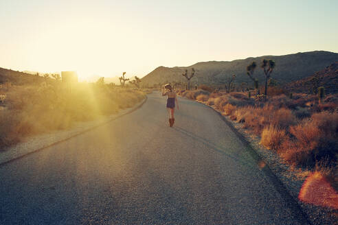 Woman jogging on country road at sunset, Joshua Tree, California, USA - CUF54036