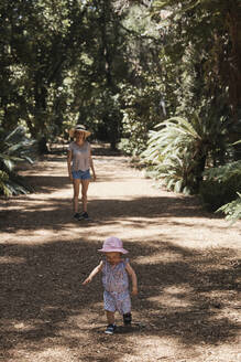 Mother and baby girl taking walk through forest - CUF54039