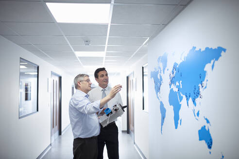 Manager and engineering designer discussing product and world map in medical scientific factory - CUF54045